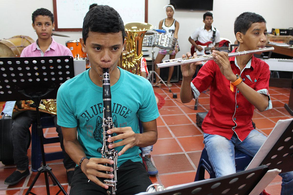 Niños apadrinados ensayan con sus instrumentos en un centro comunitario