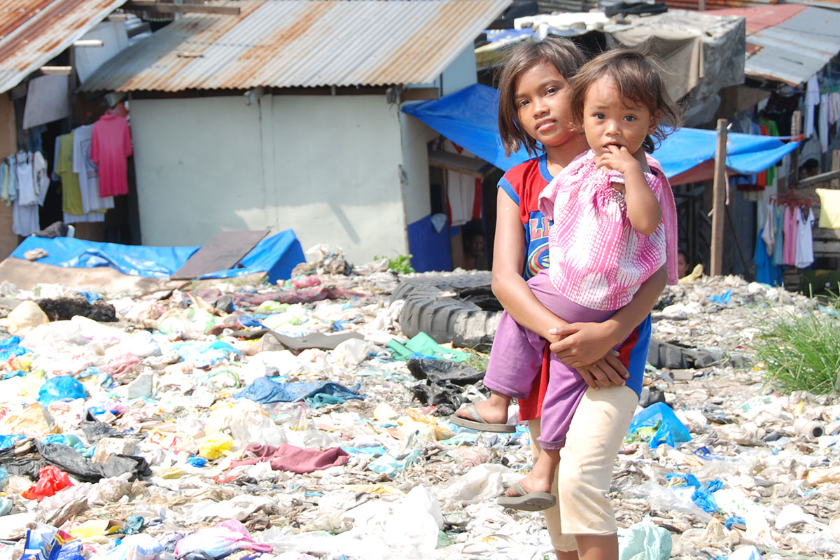 Impoverished sisters stand in a landfill near their home in Manila